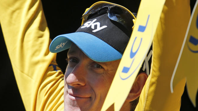 Bradley Wiggins of Britain, wearing the overall leader's yellow jersey, celebrates on the podium of the 15th stage of the Tour de France cycling race over 158.5 kilometers (98.5 miles) with start in Samatan and finish in Pau, France, Monday July 16, 2012. (AP Photo/Laurent Rebours)