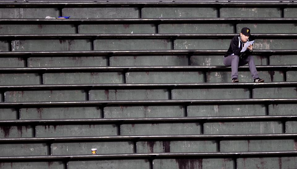 A fan sits all alone in the bleachers during the eighth inning of a baseball game between the Pittsburgh Pirates and Chicago Cubs on Tuesday, Sept. 18, 2012, in Chicago. (AP Photo/Jim Prisching)