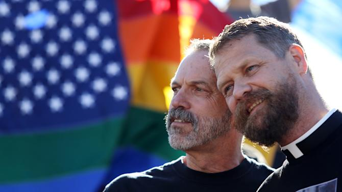 Michael Deschenes, left, and Cary Bass, who had church wedding and plan to become legally married, stand together at a celebration for the U. S. Supreme Court's rulings on Prop. 8 and DOMA in the Castro District in San Francisco, on Wednesday, June 26, 2013. In a major victory for gay rights, the Supreme Court on Wednesday struck down a provision of a federal law denying federal benefits to married gay couples and cleared the way for the resumption of same-sex marriage in California. (AP Photo/Mathew Sumner)