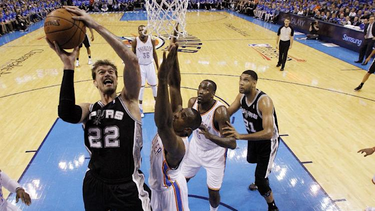 San Antonio Spurs center Tiago Splitter (22) shoots in front of Oklahoma City Thunder forward Serge Ibaka (9) in the first quarter of Game 3 of an NBA basketball playoff series in the Western Conference finals, Sunday, May 25, 2014, in Oklahoma City. (AP Photo/Sue Ogrocki)