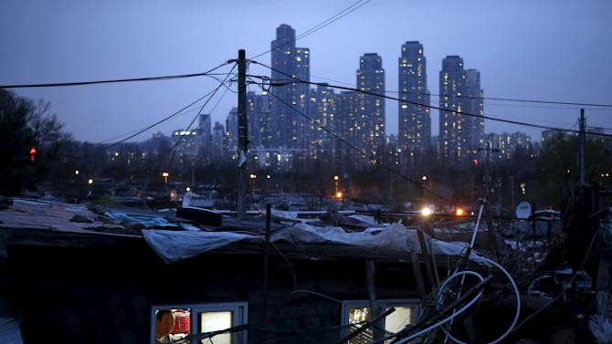 A man looks out from his shack as a luxury high-rise apartment complex is seen in the background at Guryong village in Seoul