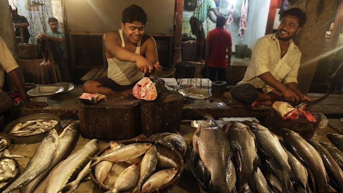 Fish sellers cut fish for customers at a market in Gauhati, India, Friday, May 30, 2014. India on Friday reported economic growth of 4.7 percent for the last fiscal year, falling short of the government's forecast and continuing a trend of sluggish expansion that helped sweep a new government to power this month. (AP Photo/Anupam Nath)