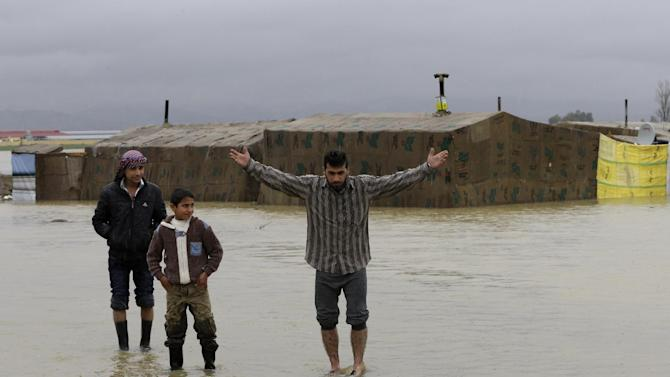 A Syrian refugee man, right, gestures as he stands in flooded water at a temporary refugee camp, in the eastern Lebanese Town of Al-Faour near the border with Syria, Lebanon, Tuesday, Jan. 8, 2013. Two Syrian refugee encampments in Lebanon's eastern Bekaa valley  were completely immersed in water Tuesday after the Litani river flooded and the water came pouring into their tents. The flood forced dozens of Syrian refugees to leave in search for alternative shelter along with their water-soaked and muddied belongings. (AP Photo/Hussein Malla)