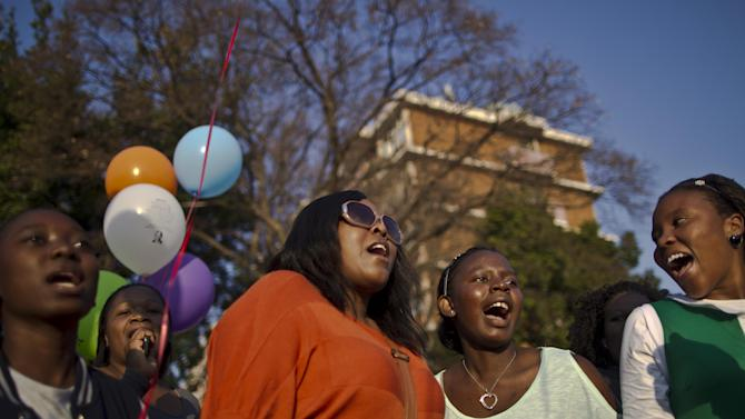 Well wishers sing songs in support of former South African President Nelson Mandela outside the Mediclinic Heart Hospital where he is being treated in Pretoria, South Africa Sunday, July 7, 2013. South Africa's anti-apartheid hero, who was admitted June 8 for a recurring lung infection, has now spent a month in the hospital. (AP Photo/Muhammed Muheisen)