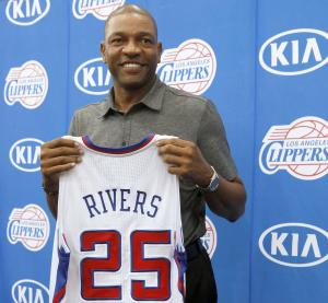 Former Boston Celtics head coach Doc Rivers holds his new Los Angeles Clippers jersey during a press conference in Los Angeles on Wednesday, June 26, 2013. Rivers was introduced as the Clippers' new coach and senior vice president of basketball operations. (AP Photo/Nick Ut)