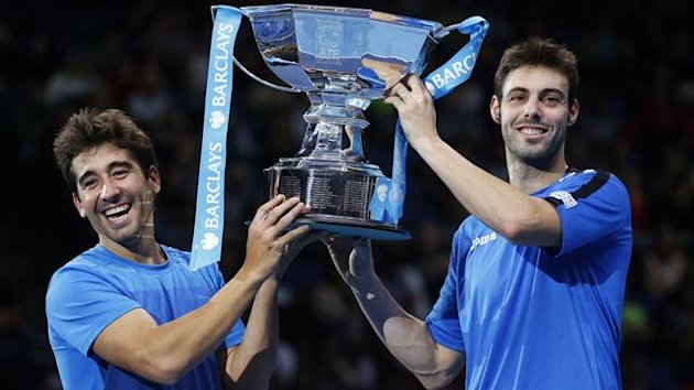 Spain's Marcel Granollers (R) and Marc Lopez hold the trophy after defeating India's Mahesh Bhupathi and Rohan Bopanna in their doubles final tennis match at the ATP World Tour Finals at the O2 Arena