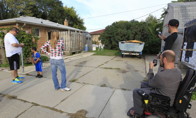 FILE - In this Sept. 26, 2012, file photo, people photograph a driveway in Roseville, Mich. that a tipster said could be the final resting place of missing Teamsters leader Jimmy Hoffa. Authorities plan to take soil samples from under the driveway. Hoffa's mysterious disappearance, assumed death and myriad searches for his body have been the stuff of urban legends for more than three decades. (AP Photo/Carlos Osorio, File)