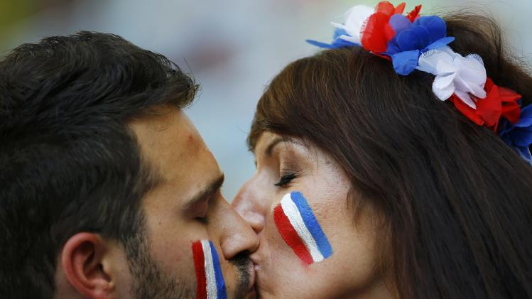 Fans of France kiss before their 2014 World Cup Group E soccer match against Ecuador at the Maracana stadium in Rio de Janeiro