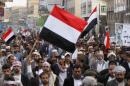 Protesters wave Yemeni national flags as they march during demonstration organized by Shi'ite Houthi movement to demand the government to rescind decision to curb fuel subsidies in Sanaa