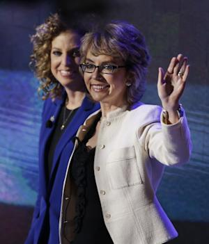 Former Rep. Gabrielle Giffords, right, walks with Democratic National Committee Chairwoman Rep. Debbie Wasserman Schultz, from Florida, to recite the Pledge of Allegiance the Democratic National Convention in Charlotte, N.C., on Thursday, Sept. 6, 2012. (AP Photo/Lynne Sladky)