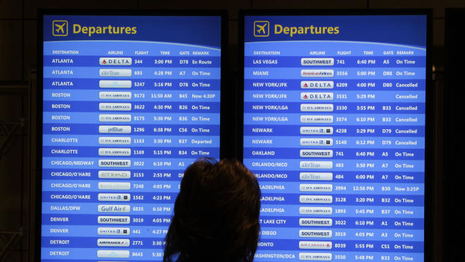 A passenger checks the departures board at Pittsburgh International Airport in Imperial, Pa, Wednesday, Oct. 31, 2012. Travel in the Northeast creaked back into motion on Wednesday, a grinding, patchy recovery that made it clear that stranded travelers will struggle to get around for days to come.(AP Photo/Gene J. Puskar)