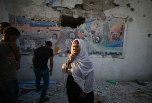 Palestinian woman looks on as she stands at a United Nations-run school sheltering Palestinians displaced by an Israeli ground offensive, that witnesses said was hit by Israeli shelling, in Jebalya refugee camp in the northern Gaza Strip