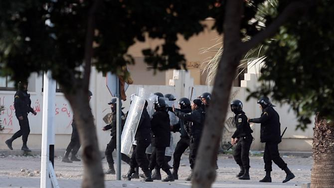 """Riot police officers run toward Tunisian protesters during clashes, in Siliana, Tunisia, Saturday, Dec. 1, 2012. The army moved into a southwestern Tunisian town, an official and witnesses said Friday, the fourth day of protests that have injured more than 300 people. President Moncef Marzouki said on television that the North African country's government has not """"met the expectations of the people"""" and asked that a new one, smaller and specialized to deal with the unrest, be formed. The current government has about 80 members. (AP Photo/Amine Landoulsi)"""