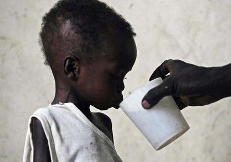 Malnourished two-year-old Dhoah Thoan is fed at a hospital ward in Akobo in southeastern Sudan's Jonglei state