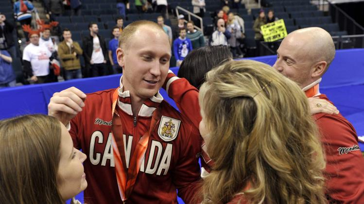 Skip Jacobs hugs women's gold medallist Jones after defeating Team Morris during the men's final at the Roar of the Rings Canadian Olympic Curling Trials in Winnipeg