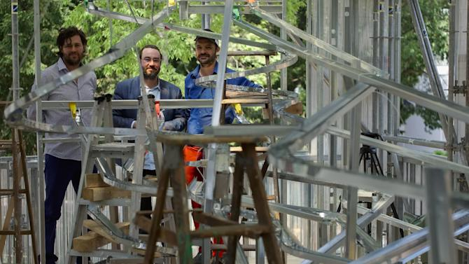 Canadian art collective BGL, from left, Nicolas Laverdiere, Sebastien Giguere, and Jasmin Bilodeau pose with their installation that lets visitors drop coins into a maze of gutters that spill into the Canada Pavilion's large glassed walls at the 56th Biennale of Arts in Venice, Tuesday, May 5, 2015. (AP Photo/Domenico Stinellis)