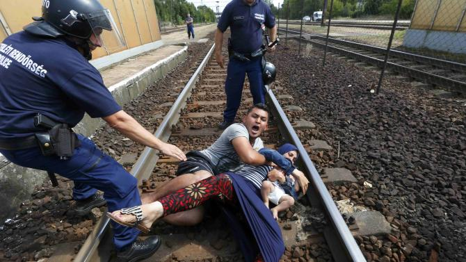 Hungarian policemen stand by the family of migrants protesting on the tracks at the railway station in the town of Bicske