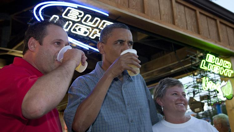 President Barack Obama has a beer with Mike Cunningham III, left, and another worker at the beer stand during a visit to the Iowa State Fair, Monday, Aug. 13, 2012, in Des Moines, Iowa. The president is on a three-day campaign bus tour through Iowa. (AP Photo/Carolyn Kaster)