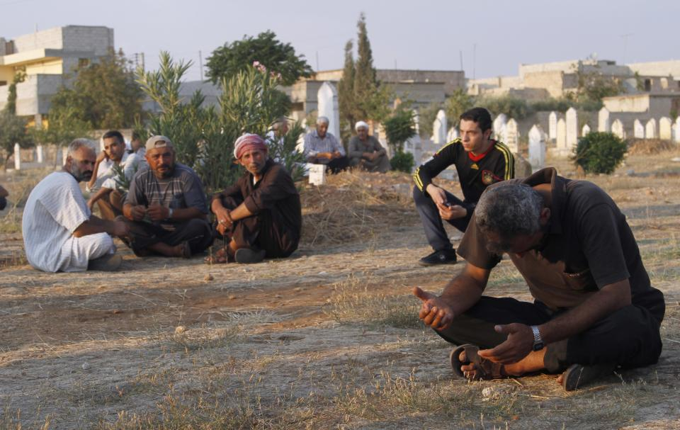 Syrians react after the funeral of 29 year-old Free Syrian Army fighter, Husain Al-Ali, who was killed during clashes in Aleppo, in the cemetery in the town of Marea on the outskirts of  Aleppo city, Syria, Thursday, Aug. 9, 2012. (AP Photo/ Khalil Hamra)