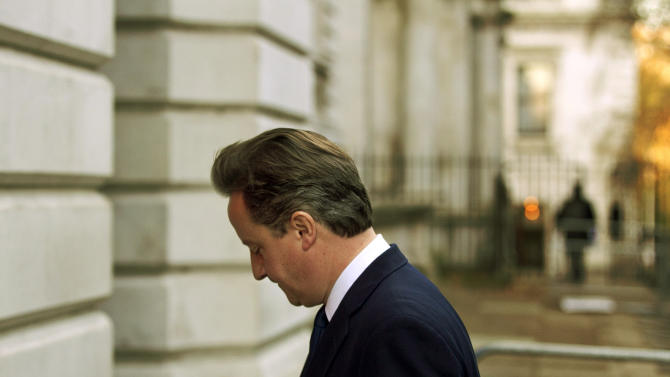 Britain's Prime Minister David Cameron leaves Downing Street in London, to go to the weekly Prime Minister's Questions session at the Houses of Parliament, Wednesday, Dec. 7, 2011.  (AP Photo/Matt Dunham)