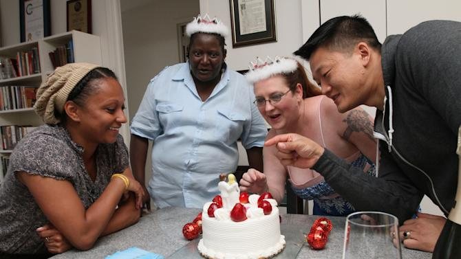 In this Wednesday, July 20, 2011, photo, Dan Choi, right, points to the cake topper of two women as Ada Ospina, left, Kawane Harris, second from left, and Harris' partner Jeanette Coleman look on during a bachelorette party for Harris and Coleman at Choi's apartment in New York. Days before New York's first gay weddings, some couples are holding traditional bachelor parties and showers while others are putting twists on tradition. (AP Photo/Tina Fineberg)