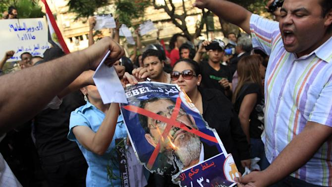 "Egyptian protesters burn a poster with the photo of Egyptian President Mohammed Morsi with Arabic that reads, "" Rebel, Muslim Brotherhood will fall on June 30 at the Itihadiya Palace,"" in front of the Culture Ministry in Cairo, Egypt, Tuesday, June 11, 2013. Fears that protests on June 30 will result in bloodshed were heightened when opposition protesters nabbed at least six pro-Morsi supporters outside the Culture Minister's office in Zamalek on Tuesday. An Associated Press reporter witnessed the protesters beating bearded men with their fists, kicking them and stoning them as they outnumbered riot police trying to intervene. (AP Photo/Khalil Hamra)"