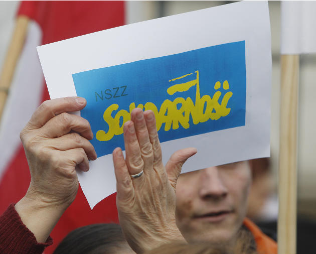 A woman holds the Solidarity trade union emblem printed in Ukraine's national colors during a march in downtown Warsaw, Poland, on Saturday, March 8, 2014, in support of Ukraine's pro-European Union d