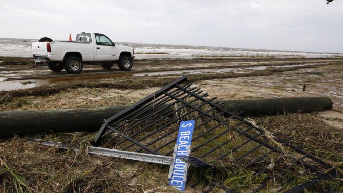 Isaac's fury damaged much of Beach Boulevard and some of the lining private property as this street sign and fencing can attest in Waveland, Miss., Thursday, Aug. 30, 2012. Although the hurricane has been downgraded Gulf Coast residents are still dealing with the wet aftermath of wide spread flooding, especially during the morning at high tide. (AP Photo/Rogelio V. Solis)