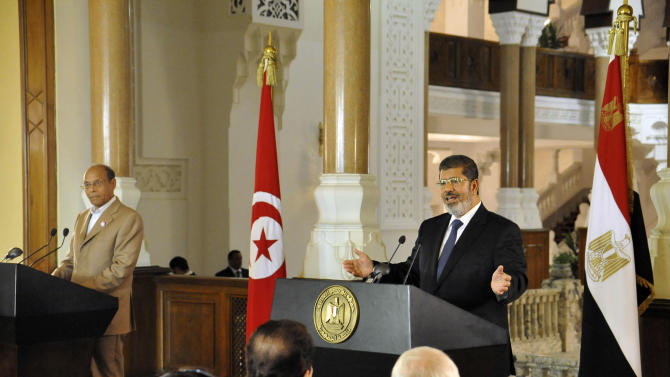 In this photo released by the Egyptian Presidency, Tunisian President Moncef Marzouki, left, listens as Egyptian President Mohammed Morsi, right, speaks to reporters during a joint news conference at the Presidential palace in Cairo, Egypt, Friday, July 13, 2012. The presidents of Egypt and Tunisia pledged to open a new chapter in relations following uprisings that overthrew longtime rulers, replacing them with a Muslim Brotherhood figure and an activist who was exiled. (AP Photo/Egyptian Presidency)