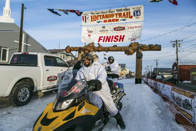 Snow mobilers come off the Iditarod trail during the Iditarod dog sled race in Nome