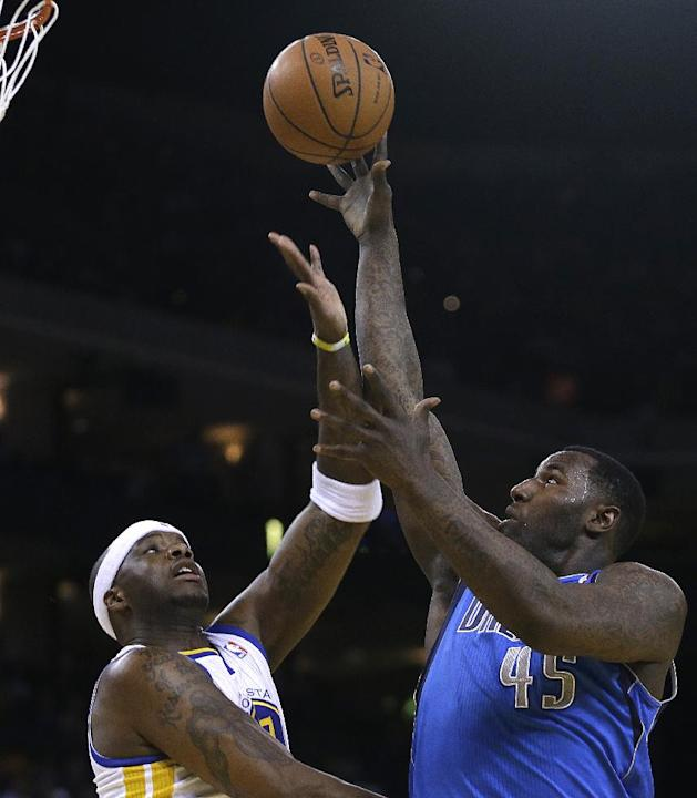 Dallas Mavericks' DeJuan Blair, right, shoots over Golden State Warriors' Jermaine O'Neal during the first half of an NBA basketball game, Tuesday, March 11, 2014, in Oakland, Calif
