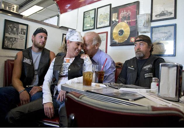 FILE - In this Sept. 9, 2012 file photo, Vice President Joe Biden talks to customers, including a woman who pulled up her chair in front of the bench Biden was sitting on, during a stop at Cruisers Di