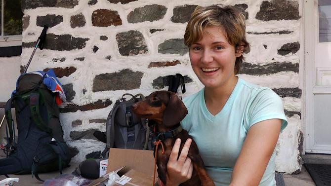 In an Aug. 1, 2012 photo, Crystal Stroud, 26, of Mississippi, rests and re-supplies with her 3-year-old Dachsund, Polly, in  Harpers Ferry, W.Va. Stroud is hiking the Appalachian Trail northward from Georgia to Maine this summer. Like the people who hike it, the Appalachian Trail is always moving. Technically, Tuesday marks the 75th anniversary of its completion. But the 2,180-mile path stretching across 14 states from Springer Mountain, Ga., to Katahdin, Maine, is never really finished. (AP Photo/Vicki Smith)