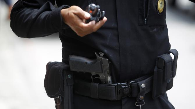 A gun, which according to police belonged to a suspected gunman who was arrested, is seen tucked into the belt of a police officer after it was seized following a shooting at a downtown street of Guatemala City