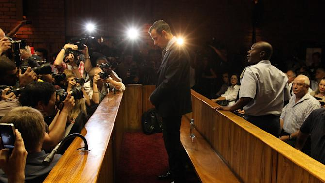 In this photo taken Friday, Feb. 22, 2013, Olympic athlete Oscar Pistorius appears in court during his bail hearing in Pretoria, South Africa, for the shooting death of his girlfriend Reeva Steenkamp. A spokeswoman for Oscar Pistorius says he has reported to authorities under the bail terms in the murder case against him in Preoria, Monday, Feb. 25, 2013. AP Photo/Themba Hadebe)