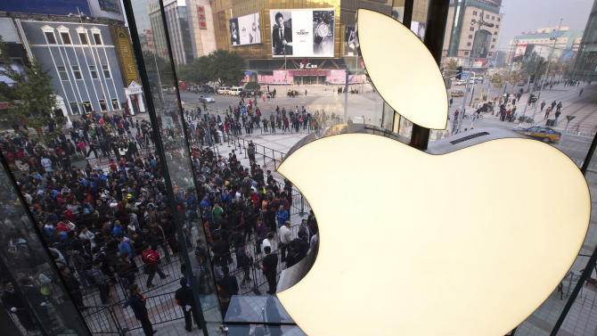 FILE - In this Oct. 20, 2012 photo, Chinese people line up to enter a newly-opened Apple Store in Wangfujing shopping district in Beijing. A Chinese court has ordered Apple Inc. to pay 1.03 million yuan ($165,000) to eight Chinese writers and two companies who say unlicensed copies of their work were distributed through Apple's online store. The Beijing No. 2 Intermediate People's Court ruled Thursday, Dec. 27, 2012 that Apple violated the writers' copyrights by allowing applications containing their work to be distributed through its App Store, according to an official who answered the phone at the court and said he was the judge in the case. (AP Photo/Andy Wong, File)