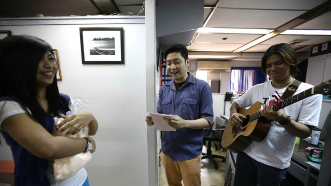 Rose Natividad, left, reacts as a singer, hired by her partner who is working for a cruise liner overseas, serenades her as a surprised Valentine's Day gift to her at her office in Manila, Philippines Thursday Feb. 14, 2013. The unique surprise serenade service, which includes love songs, a cuddly teddy bear, and a video recording of the romance-by-proxy event that is shipped to the client abroad, is played out in restaurants, offices and homes across the Philippines on Valentine's Day. (AP Photo/Bullit Marquez)
