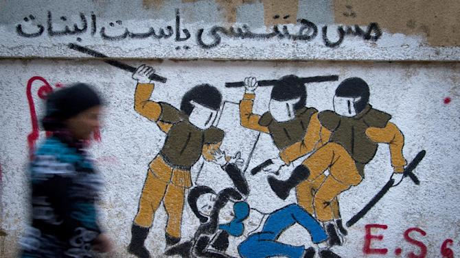 """An Egyptian woman passes by a new mural inspired by a widely circulated photo of Egyptian police beating and stripping a veiled female protester, on a recently whitewashed wall in Tahrir Square, Cairo, Egypt, Friday, Sept. 28, 2012. The Arabic writing reads, """"we will not forget you.""""(AP Photo/Khalil Hamra)"""
