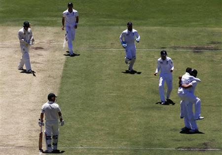 England's captain Cook celebrates with team mate Swann after he caught Australia's Clarke for 24 runs during first day of third Ashes cricket test in Perth