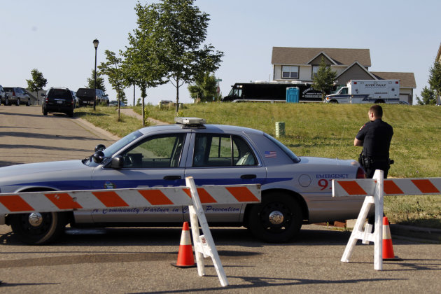 River Falls police block off the street near the crime scene Wednesday, July 11, 2012 in River Falls, Wis. Three young sisters were found Tuesday afternoon when police were asked by their mother to check on their welfare. Officers say there was an odor of gas when they entered the house. Their father was arrested and remains in jail pending charges. (AP Photo/The Star Tribune, Jerry Holt) MANDATORY CREDIT; ST. PAUL PIONEER PRESS OUT; MAGS OUT; TWIN CITIES TV OUT