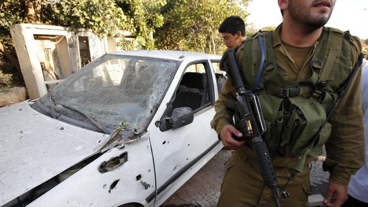 An Israeli soldier walks past a car damaged by a barrage of Lebanese rockets fired at Israel, in Kibbutz Gesher HaZiv, near Nahariya