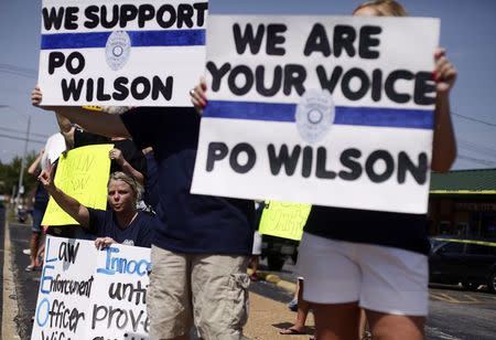 Demonstrators supporting Ferguson Police officer Darren Wilson hold signs during a rally in St. Louis