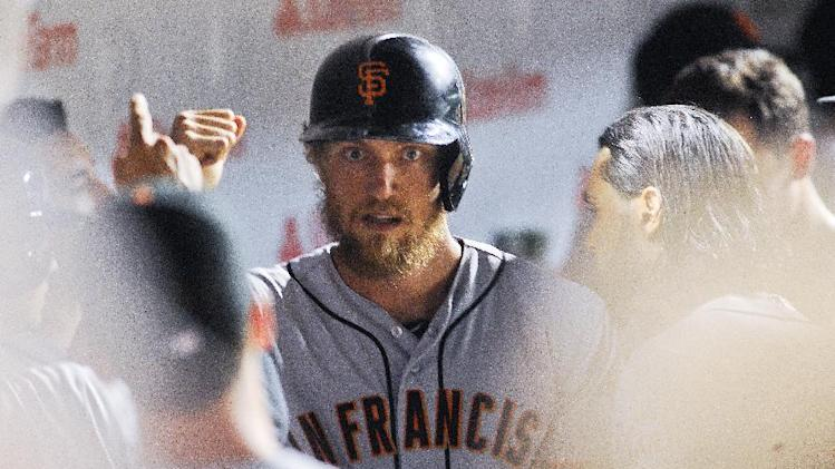 San Francisco Giants Hunter Pence celebrates in the dugout after he hit a home run in the fourth inning of an baseball game against the Chicago Cubs on Saturday, Aug. 20, 2014, in Chicago. (AP Photo/Matt Marton)