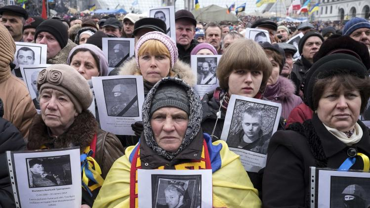 People hold portraits of people killed in recent violence as they