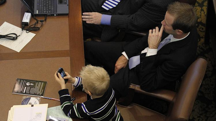 Kase Williams, 6, plays on a phone as his dad, Rep. Cory Williams of Stillwater, listens to Oklahoma Gov. Mary Fallin deliver her State of the State address on the floor of the Oklahoma House in Oklahoma City, Monday, Feb. 6, 2012. (AP Photo/Garett Fisbeck)