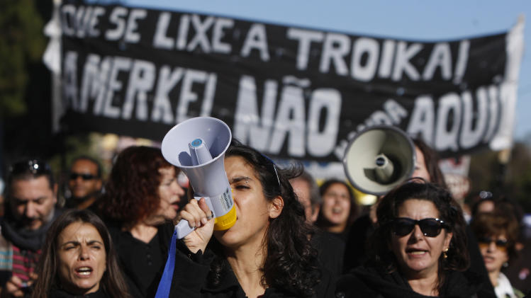 Demonstrators hold banners protesting the visit to Portugal of German Chancellor Angela Merkel Monday, Nov. 12 2012, in Lisbon. Protest marches were planned during Merkel's six-hour stay when she was to hold talks with Prime Minister Pedro Passos Coelho and President Anibal Cavaco Silva and speak at a business conference attended by leading German and Portuguese companies. Banner reads 'Damn the Troika. Merkel's not in charge here'. (AP Photo/Joao Henriques)