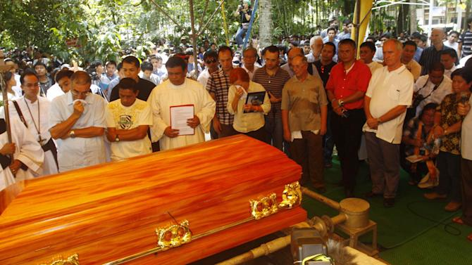 """FILE - In this Oct. 25, 2011 file photo, a crowd gather in Kidapawan township as slain Italian priest Rev. Fausto Tentorio is laid in a coffin to rest in North Cotabato province in southern Philippines. The dead last year included Tentorio, an Italian Catholic priest who fought against mining companies to protect the ancestral lands of the Manobo tribe in the southern Philippines. Affectionately known as """"Father Pops,"""" he was buried in the coffin made from a favorite mahogany tree he had planted. (AP Photo/File)"""