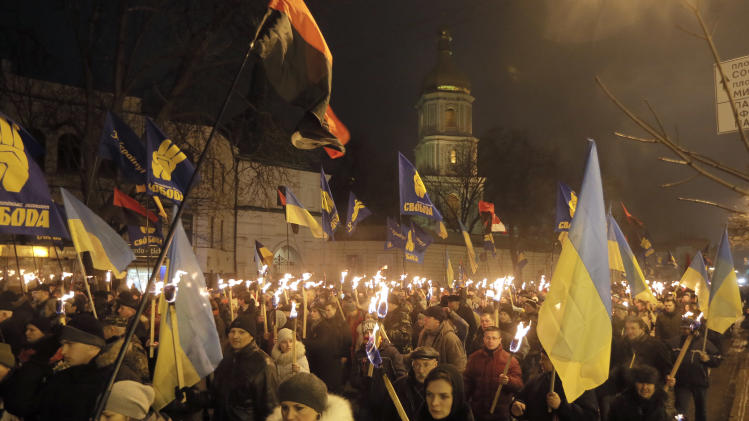 Ukrainian nationalists carry torches during a rally in downtown Kiev, Ukraine, late Wednesday, Jan. 1, 2014. The rally was organized on the occasion of the birth anniversary of Stepan Bandera, founder of a rebel army that fought against the Soviet regime. (AP Photo/Efrem Lukatsky)