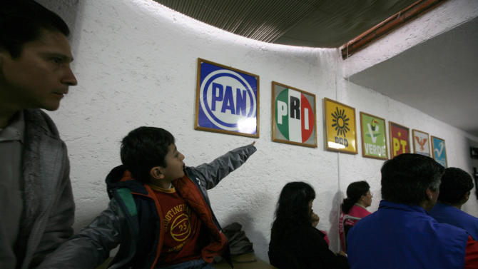 A boy points to the the logos of different political parties as he accompanies a family member during a meeting by election workers ahead of general elections in Mexico City, Saturday, June 30, 2012. Mexico will hold general elections, including the presidential election, on July 1.  (AP Photo/Marco Ugarte)