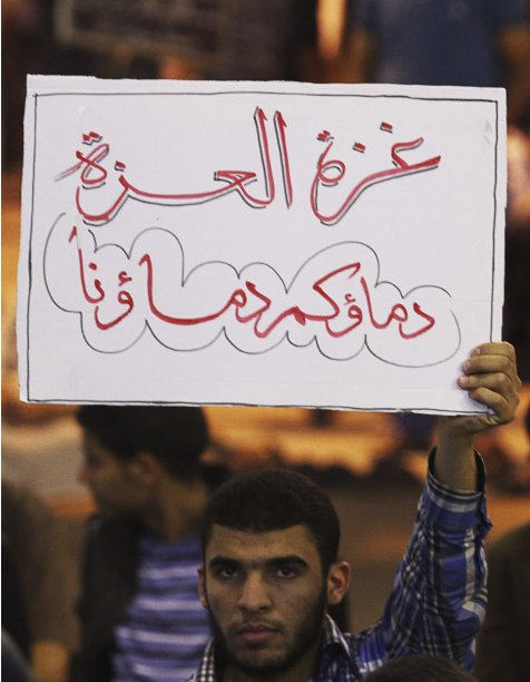 A man holds up a sign reading,